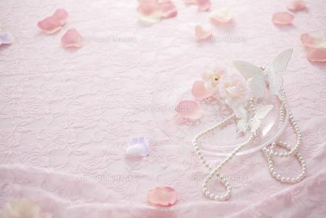 ピンクのレースの上にマニキュアとパールのネックレスと花びら FYI00961190