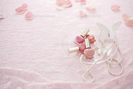 ピンクのレースの上にマニキュアとパールのネックレスと花びら FYI00961225