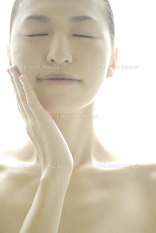 頬に手をやる女性 FYI00993716