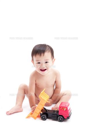裸で座りトラックのおもちゃで遊ぶ赤ちゃん FYI01016524