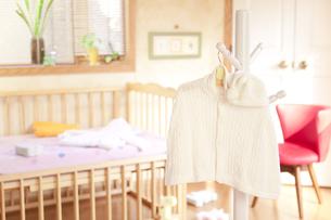 ベッドの前にあるハンガーにかけたベビー服 FYI01016697