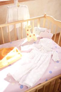 ハンガーとベッドにあるベビー服 FYI01016786