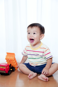 トラックのおもちゃで遊ぶ赤ちゃん FYI01016799