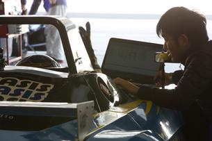 ピットで打ち合わせするレーサーとメカニック FYI01030372
