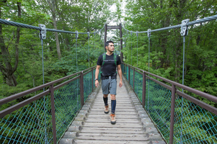 トレッキングで橋を渡る青年 FYI01030410