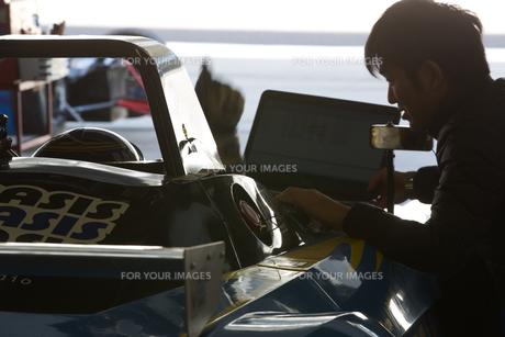 ピットで打ち合わせするレーサーとメカニック FYI01030422
