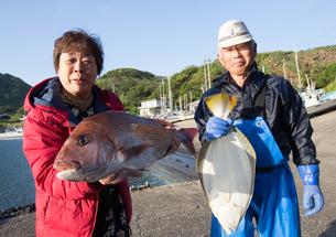漁港で魚を持つ女将と船長 FYI01030563