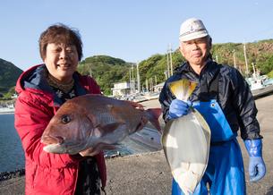 漁港で魚を持つ女将と船長 FYI01030688