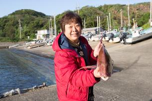 漁港で魚を持つ女将 FYI01030862