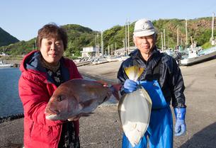 漁港で魚を持つ女将と船長 FYI01030878