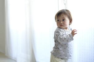 カーテンで遊ぶ赤ちゃん FYI01032097