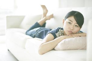 ソファーに寝転びながら何か思いふけっている女性 FYI01033173
