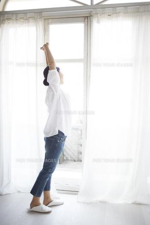 窓際でストレッチしている女性 FYI01033192
