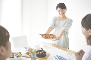 ピザを差し出す女性 FYI01033228