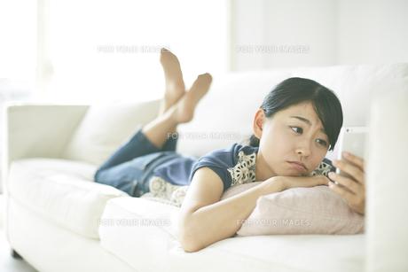 ソファーの上で携帯を見ながら寂しそうな顔をしている女性 FYI01033229