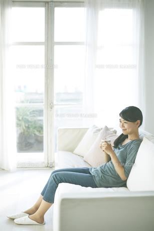 ソファーの上で飲み物を飲んでいる女性 FYI01033232