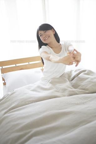 ベッドの上でストレッチをする女性 FYI01033241