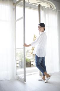 窓を開けながら振り返る女性 FYI01033255