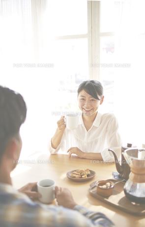 男性とコーヒーを飲みながら会話している女性の素材 [FYI01033290]