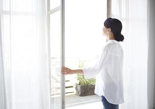 窓を開ける女性 FYI01033294
