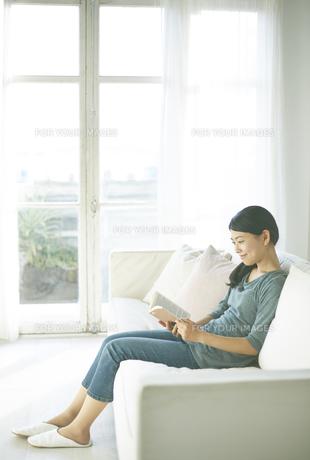ソファーの上で読書している女性 FYI01033318