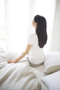 ベッドの上でストレッチをする女性 FYI01033321