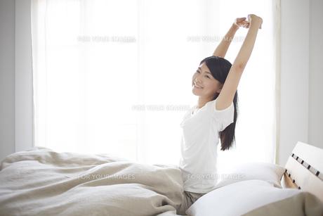 ベッドの上でストレッチをする女性 FYI01033326