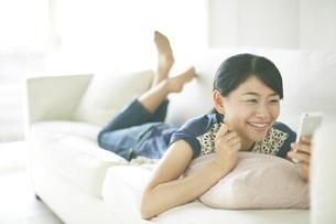ソファーの上で携帯を見ながら楽しそうな顔をしている女性 FYI01033332