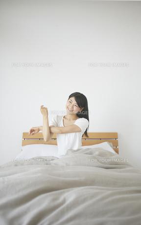 ベッドの上でストレッチをする女性 FYI01033346