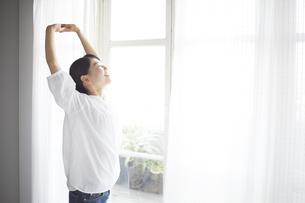 窓際でストレッチしている女性 FYI01033354