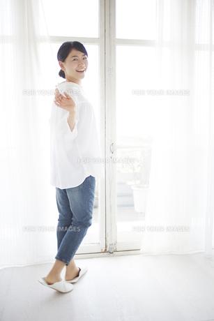 窓際で部屋の中の人に手をふる女性 FYI01033361