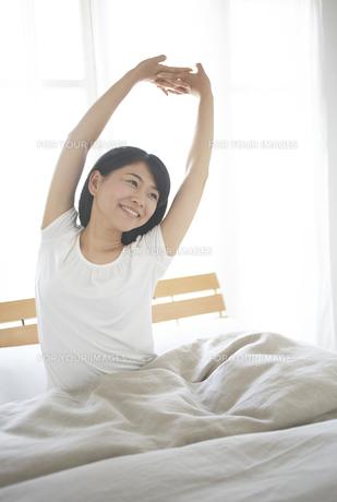 ベッドの上でストレッチをする女性 FYI01033366