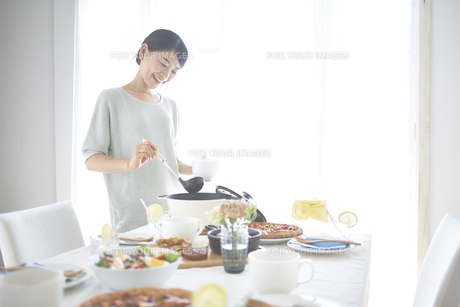 スープを取り分ける女性 FYI01033388