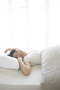 ベッドの上でストレッチをする女性 FYI01033453
