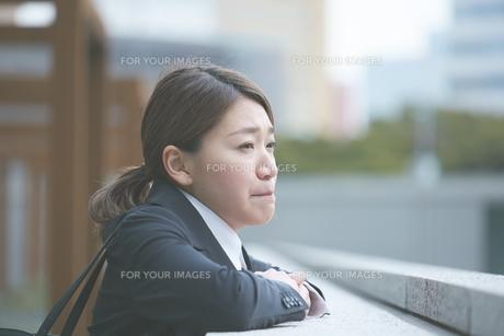 悔しそうに遠くを見つめる働く女性の素材 [FYI01033500]