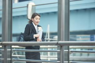 書類を持って急いでいる働く女性 FYI01033509