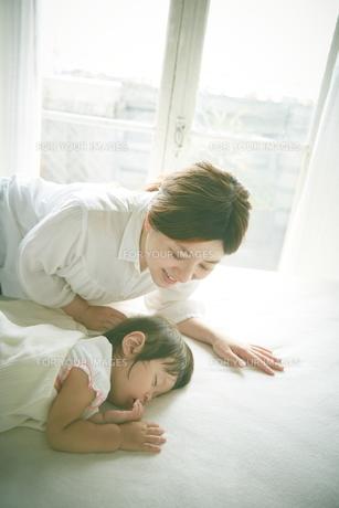 ベッドの上でお昼寝する赤ちゃんをお母さんが優しく見つめている FYI01033629