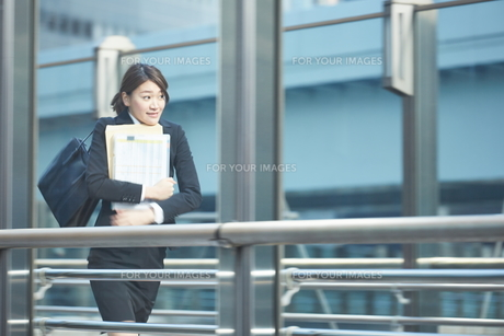 書類を持って急いでいる働く女性 FYI01033653