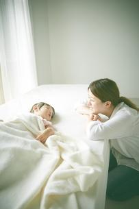 ベッドの上でお昼寝する赤ちゃんをお母さんが優しく見つめている FYI01033672