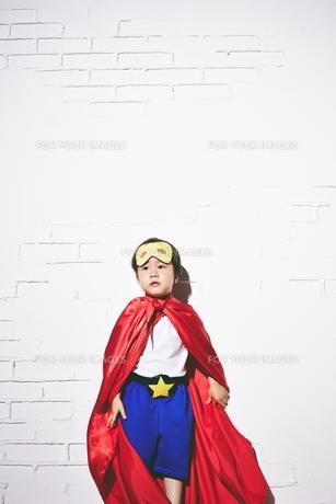 レンガの壁の前で勝利のポーズをするヒーローの男の子 FYI01033744