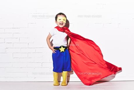 レンガの壁の前で勝利のポーズをするヒーローの男の子 FYI01033753
