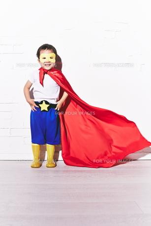 レンガの壁の前で勝利のポーズをするヒーローの男の子 FYI01033765