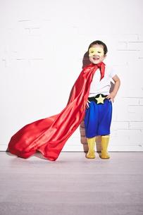 レンガの壁の前で勝利のポーズをするヒーローの男の子 FYI01033825