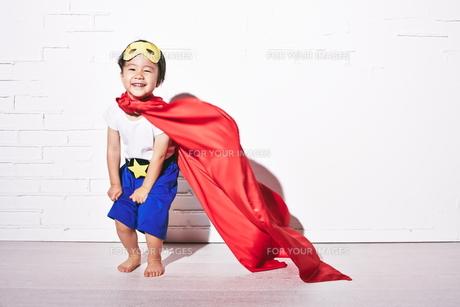 レンガの壁の前で勝利のポーズをするヒーローの男の子 FYI01033854