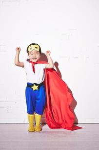 レンガの壁の前で勝利のポーズをするヒーローの男の子 FYI01033874