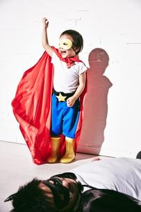 悪者をやっつけて勝利のポーズをするヒーローの男の子 FYI01033886