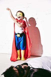 悪者をやっつけて勝利のポーズをするヒーローの男の子 FYI01033995