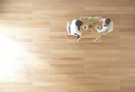 茶色の木の床とデザートを食べる夫婦 FYI01034013