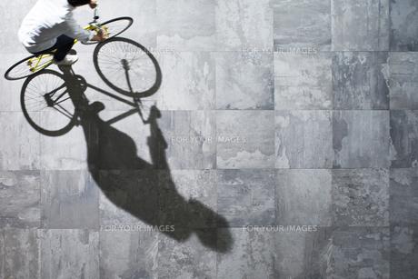 光が差し込む石の床を自転車で走る男性 FYI01034036