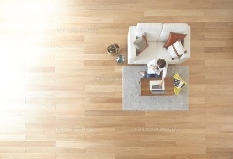 茶色の木の床とコーヒーを飲む女性 FYI01034081